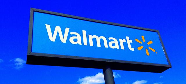 A tall Walmart sign against a clear, blue sky.