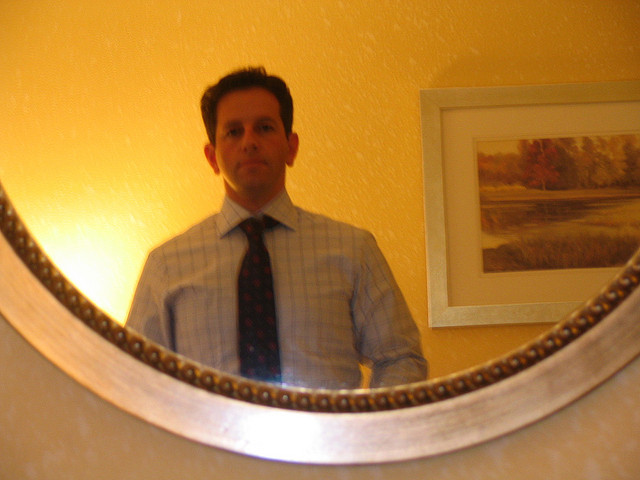 A man trying looking in a mirror while trying on a suit before his interview.