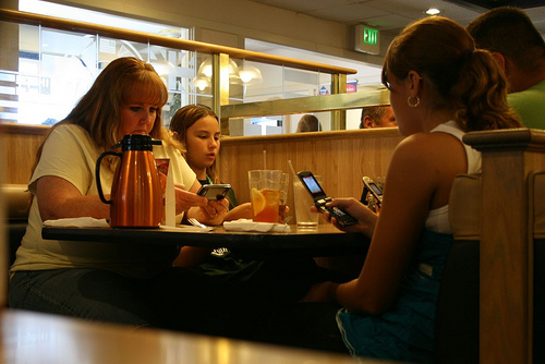 A family sitting at a table, all engrossed in their phone.