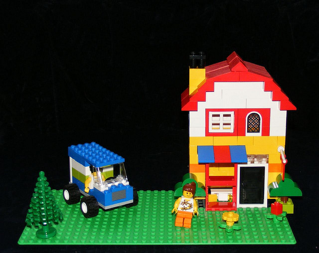 A Lego House with a car and two happy people.