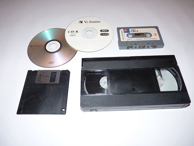An array of different media platforms (A DVD, CD-R, cassette tape, VHS, and floppy disc.