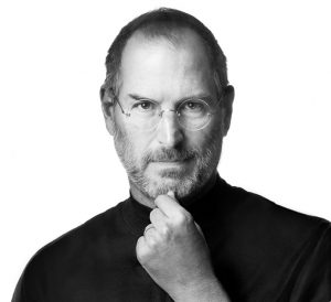 Black and white photo of Steve Jobs wearing characteristic black turtleneck and pinching his chin between forefinger and thumb.