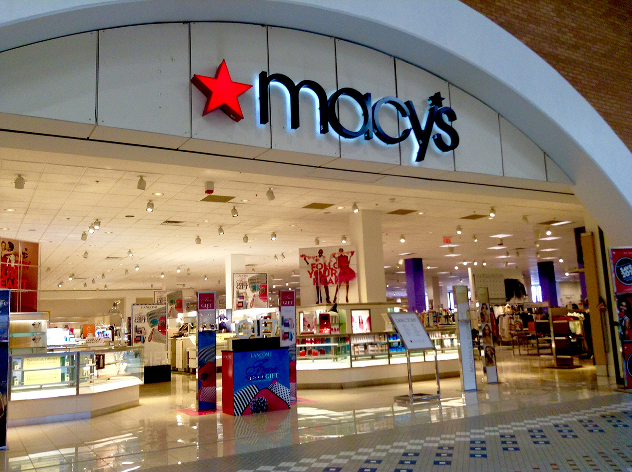Photograph shows the brightly lit entrance to a Macy's department store.