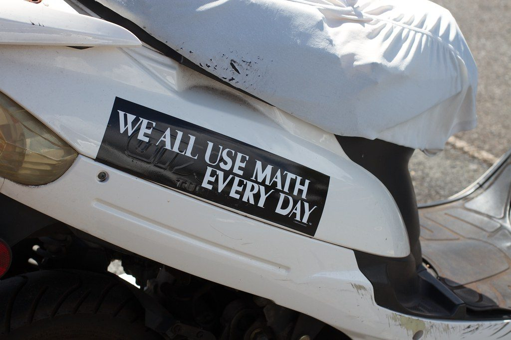 "A white car with a bumper sticker that says ""We all use math every day"""