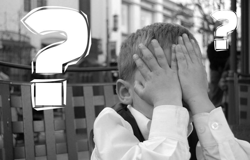 boy covering face with question marks