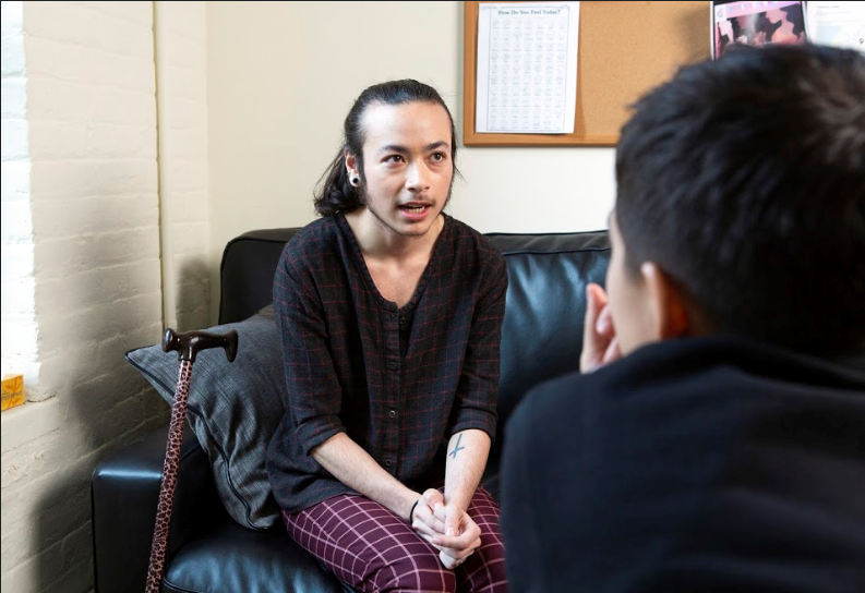 A genderqueer person sitting on a couch, talking to a therapist in a brightly-lit room